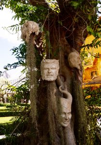 head sculptures hanging from a tree