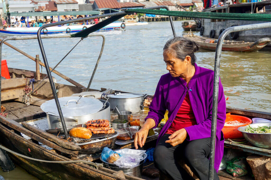 Lady serving food in a boat